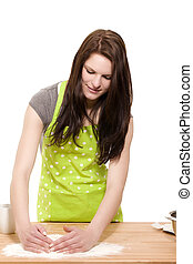 smiling young woman forming flour for baking on a table with white background