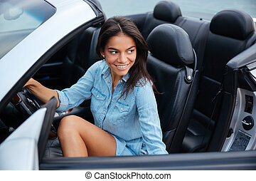 Smiling young woman getting out of her convertible car