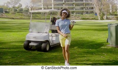 Smiling young woman golfer walking on the course in front of...