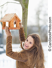 Smiling young woman hanging bird feeder on tree in winter ...