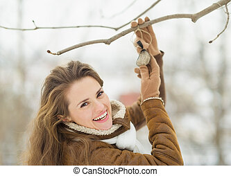 Smiling young woman hanging bird feeder on tree in winter...