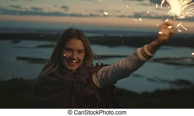 Smiling young woman have fun with sparkler at evening, slow motion