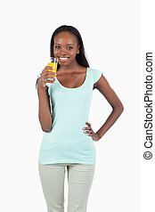 Smiling young woman having a sip of orange juice