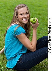 Smiling young woman holding a delicious apple while sitting down in the countryside