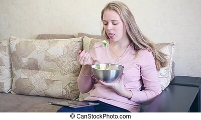 Smiling young woman holding a forkful of salad