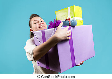 Smiling young woman holding a lot of gifts in her hands