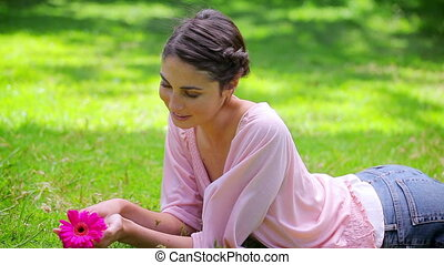 Smiling young woman holding a pink flower