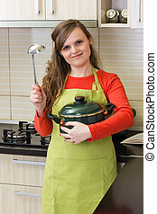 Smiling young woman  holding a pot and a soup ladle