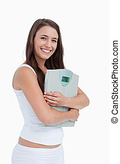 smiling young woman holding a weighing scales