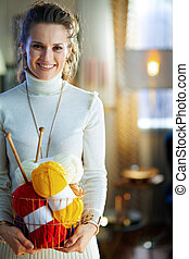 smiling young woman holding basket with yarn and needles