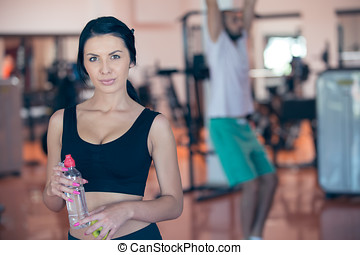 Smiling young woman holding bottle with water in gym.