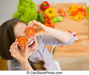 Smiling young woman holding cherry tomatoes in front of face