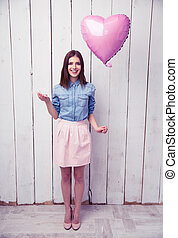 Smiling young woman holding cookies and balloon