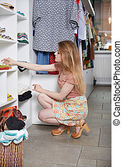Smiling young woman holding dress and smiling while standing in clothing store