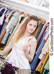 Smiling young woman holding dress a