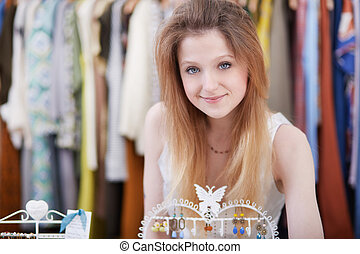 Smiling young woman holding dress