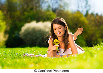 Smiling young woman holding flower