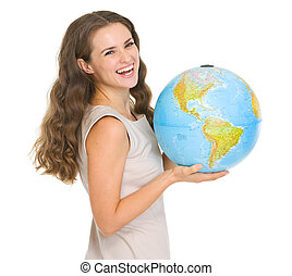 Smiling young woman holding globe