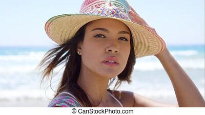 Smiling young woman holding her sunhat