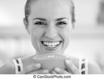 Smiling young woman holding orange slice