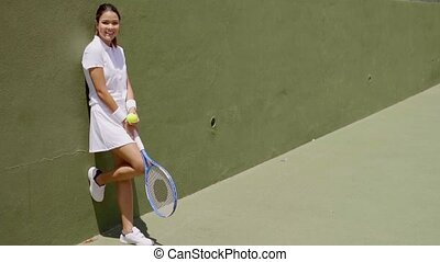 Smiling Young Woman Holding Racket on Tennis Court - Full...