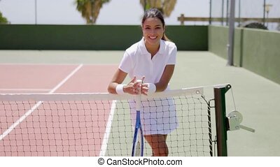 Smiling Young Woman Holding Racket on Tennis Court - Three...