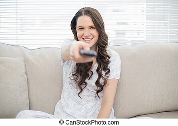 Smiling young woman holding remote sitting on a cosy couch