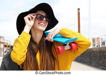 Smiling young woman holding skateboard on shoulder