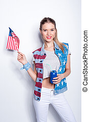 Smiling young woman holding small american flag and can with straw, woman celebrating  Independence Day of America