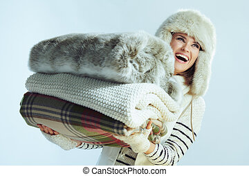 smiling young woman holding stack of warm blankets