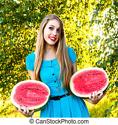 Smiling young woman holding two halfs of watermelon