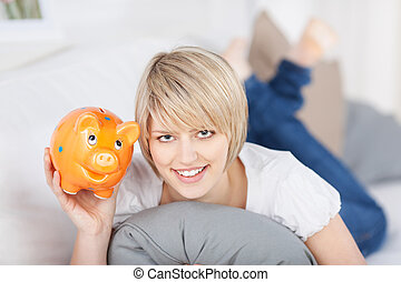 Smiling young woman holding up a piggy bank