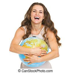 Smiling young woman hugging earth globe
