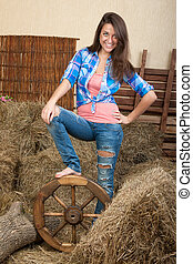 Smiling young woman in a shed with rural interior