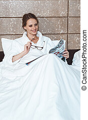 woman in bathrobe reading magazine