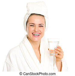 Smiling young woman in bathrobe with glass of water