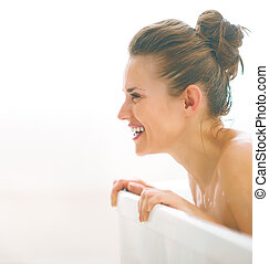 Smiling young woman in bathtub looking on copy space