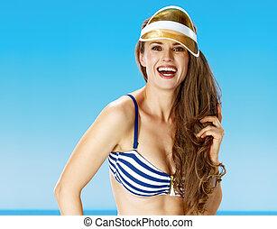 smiling young woman in bikini on seashore in yellow sun ...
