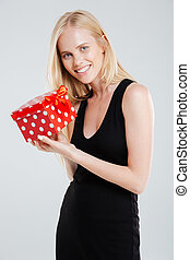 Smiling young woman in black dress holding gift box