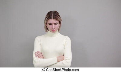 Smiling young woman in casual white sweater holding hands ...