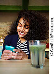 Smiling young woman in coffee shop using mobile phone