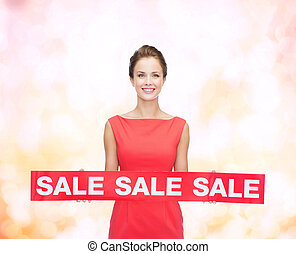 smiling young woman in dress with red sale sign