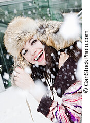 smiling young woman in falling snow
