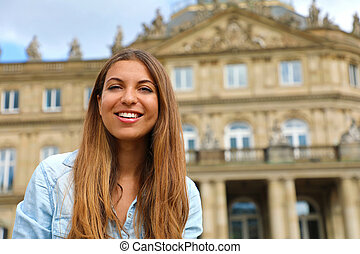 Smiling young woman in front of Neues Schloss (New Palace) of Stuttgart, Germany