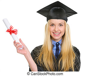 Smiling young woman in graduation gown holding diploma