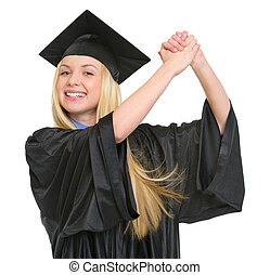 Smiling young woman in graduation gown rejoicing success