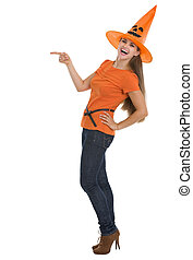Smiling young woman in Halloween hat pointing on copy space