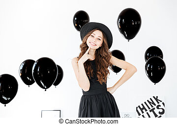 Smiling young woman in hat and dress wiith black balloons