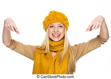 Smiling young woman in hat and scarf pointing down on copy space