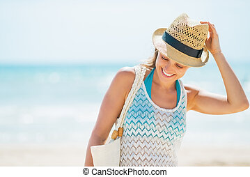 Smiling young woman in hat on beach